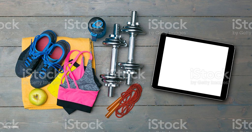 fitness equipment and blank digital tablet on gym floor stock photo
