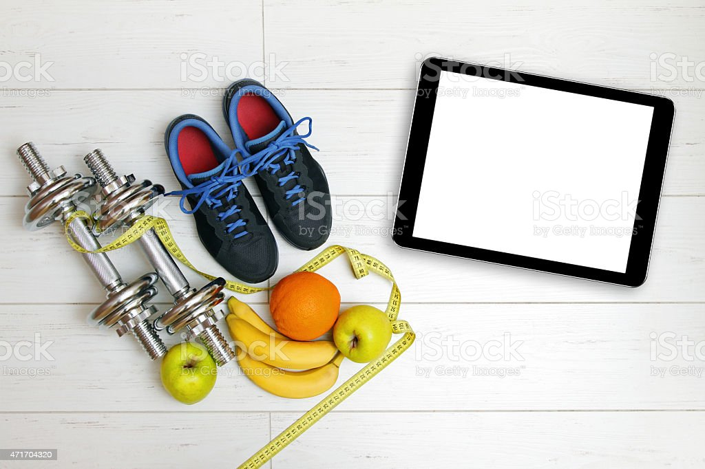 fitness equipment and fruits on wooden plank floor stock photo