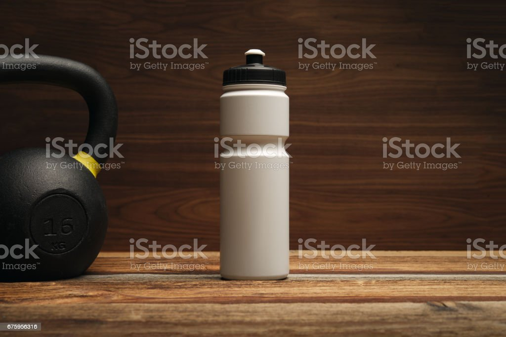 Fitness equipment and supplements on wooden floor in gym Fitness background with Water bottle shaker and Kettlebell Free copy space stock photo