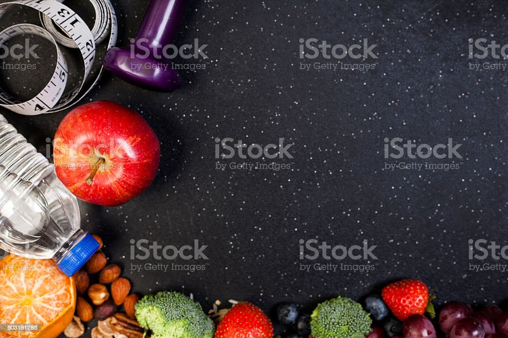 Fitness, exercise themed scene with dumbbells, water, fruit. stock photo