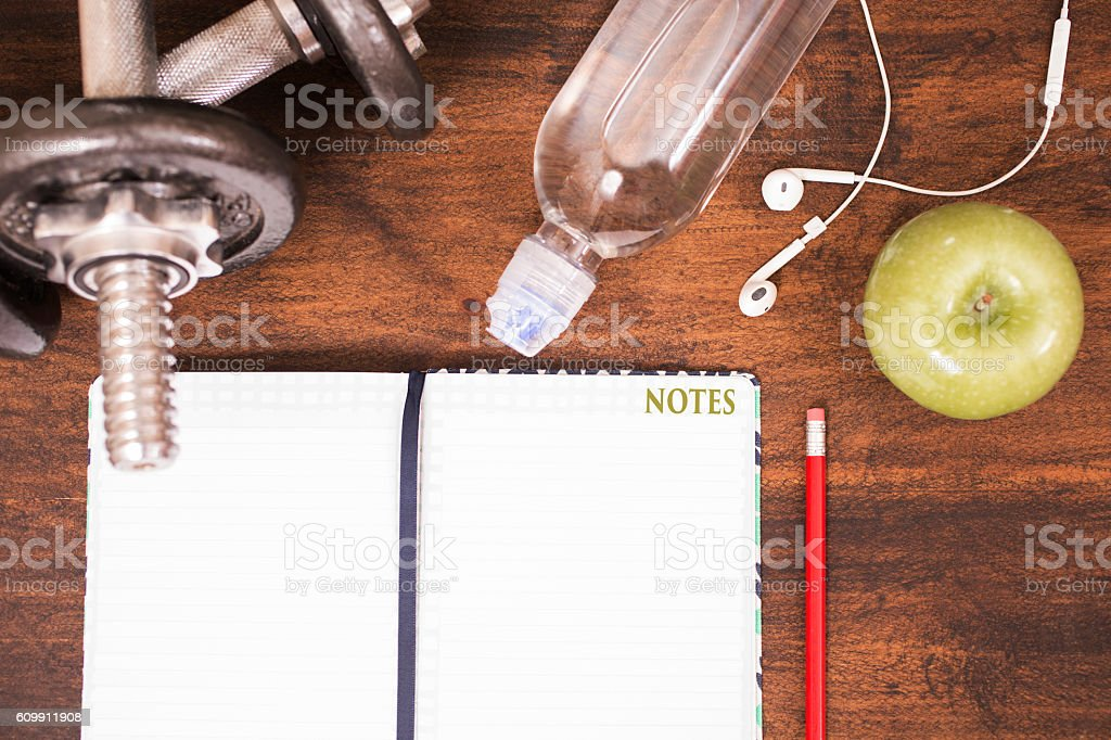 Fitness, exercise themed scene with weights, earbuds, apple, journal. stock photo