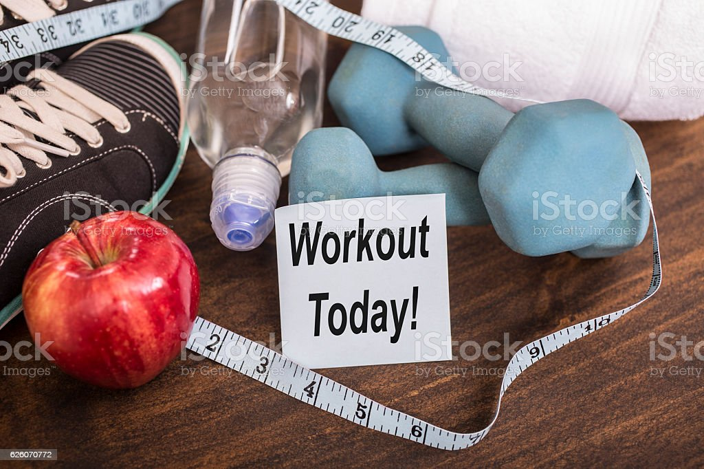 Fitness, exercise themed scene with weights, sneakers, apple. stock photo