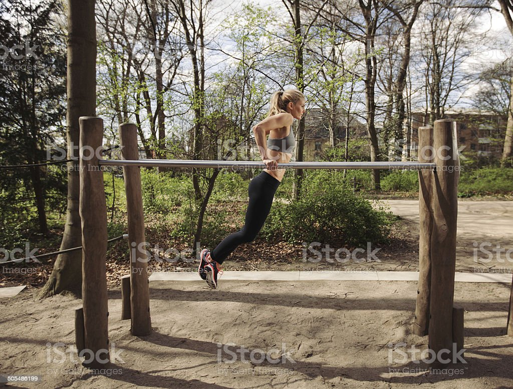Fitness female doing parallel bar dips stock photo