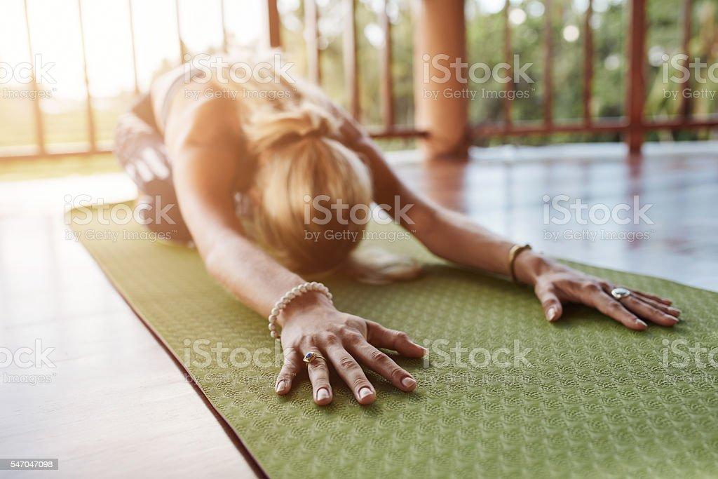 Fitness female performing balasana yoga at gym stock photo