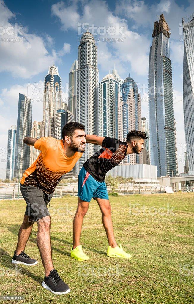 fitness friends doing stretching in dubai marina stock photo