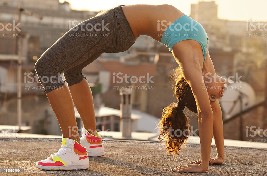 fitness girl doing bridge exercise on the roof royalty-free stock photo