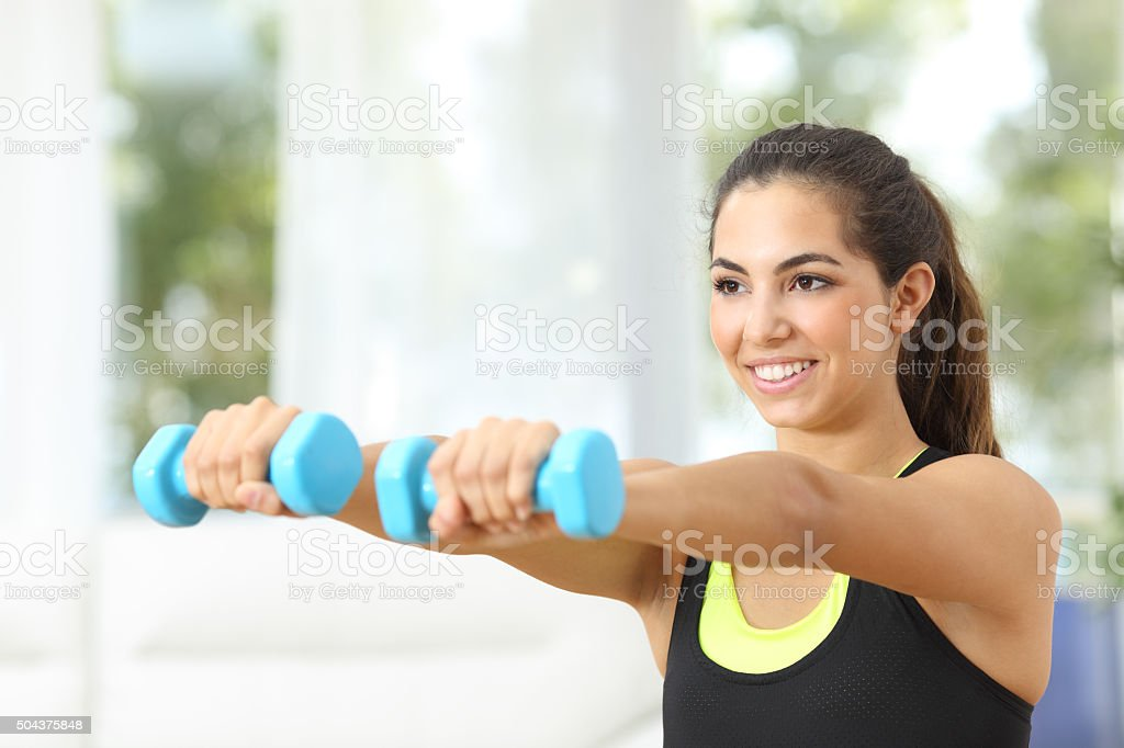 Fitness girl doing weights at home stock photo