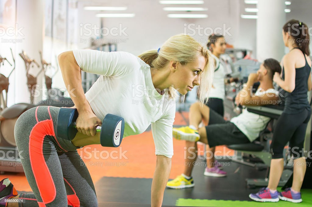 Fitness girl lifting dumbbell in gym. stock photo