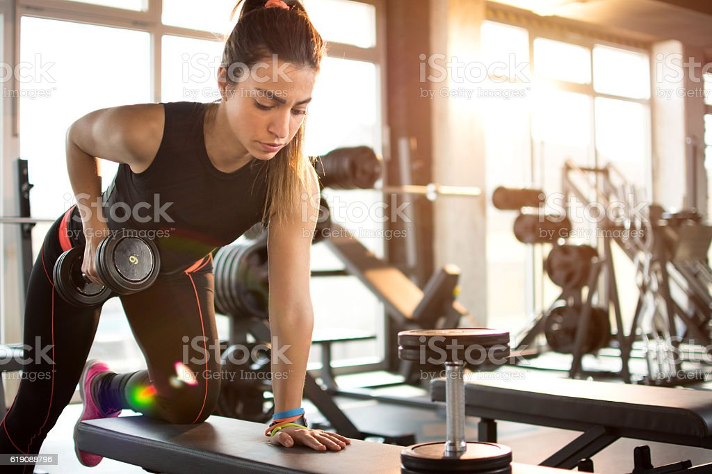 Fitness girl lifting dumbbell in the morning. stock photo
