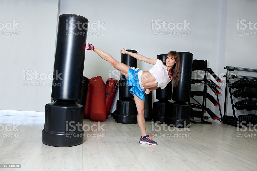 Fitness girl making karate in a gym stock photo