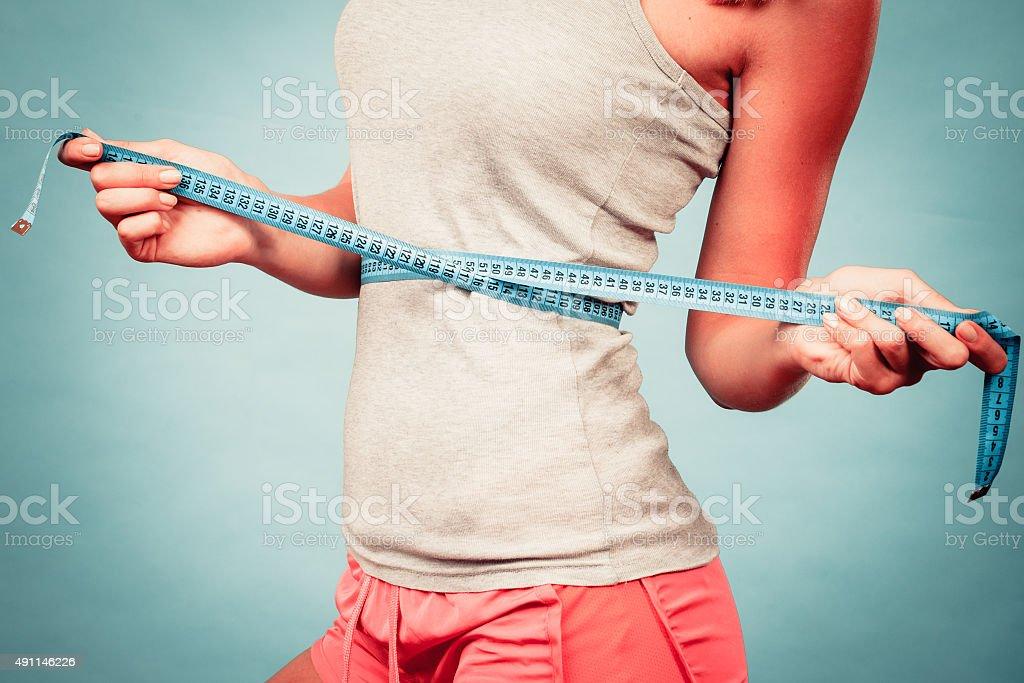 Fitness girl measuring her waistline stock photo