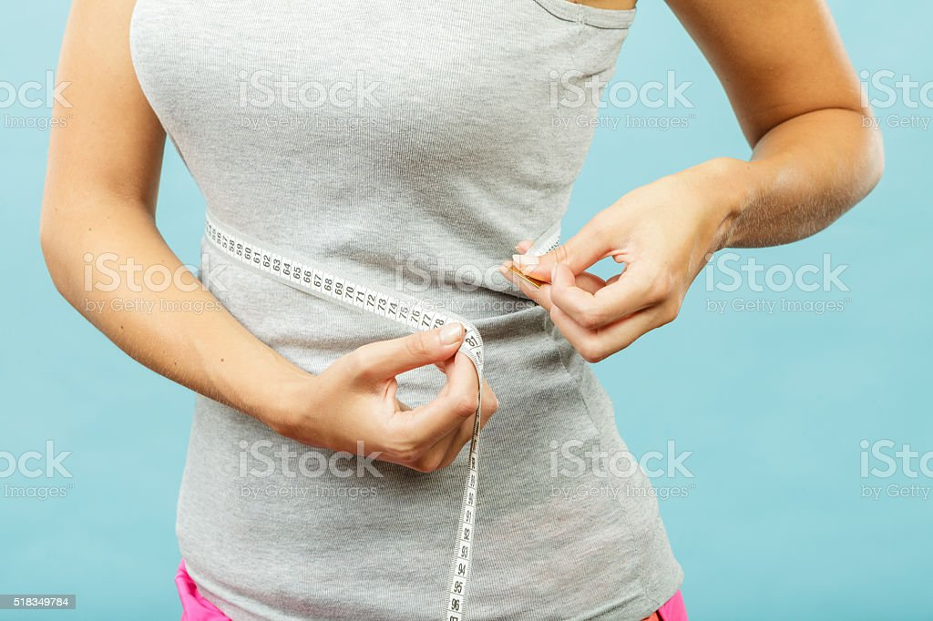 Fitness girl measuring her waistline stock photo