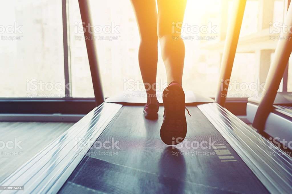 Fitness girl running on treadmill stock photo