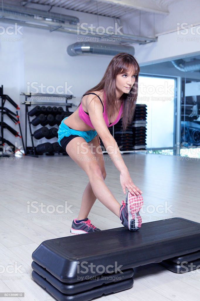 fitness girl step stretching stock photo
