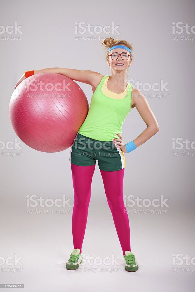 Fitness girl with glasses holding pink pilates ball royalty-free stock photo