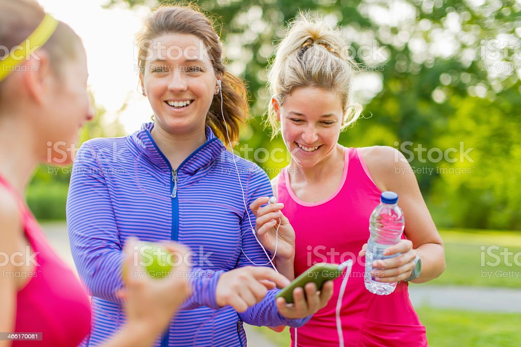 Fitness girls have fun listening music with earbuds at park stock photo