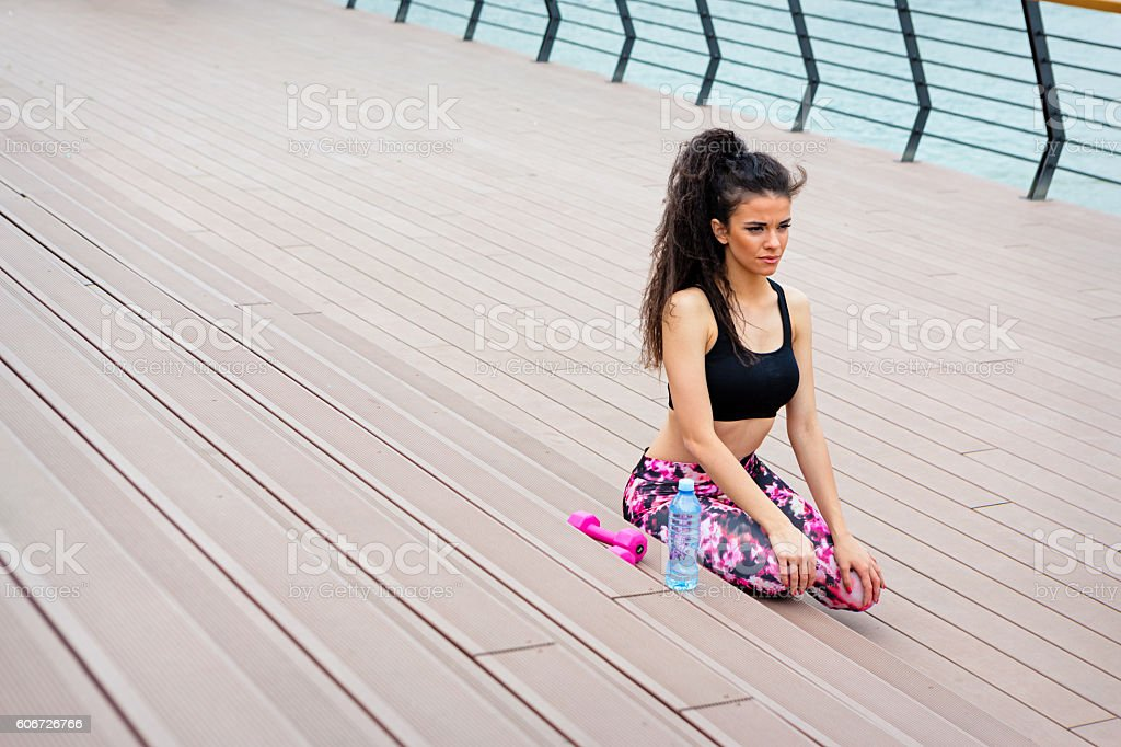 Fitness girls work out by the river. Pink dumbbels and bottle of...