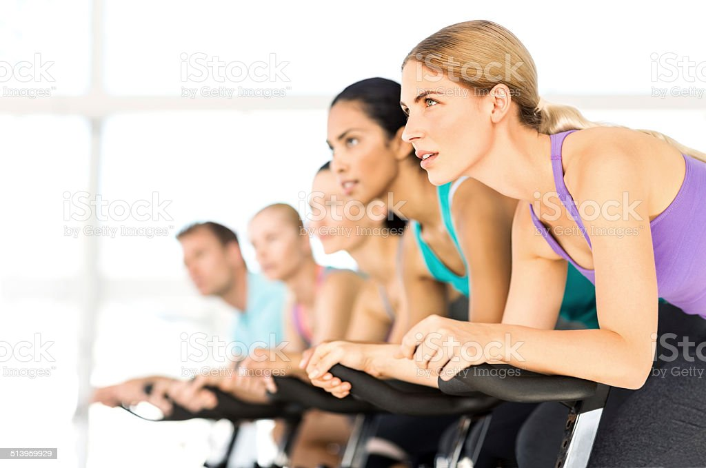 Fitness Group Exercising On Spin Bikes In Gym stock photo