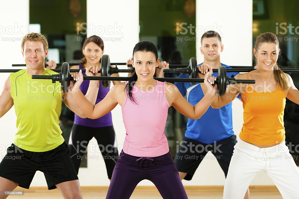 Fitness group with barbell in gym stock photo