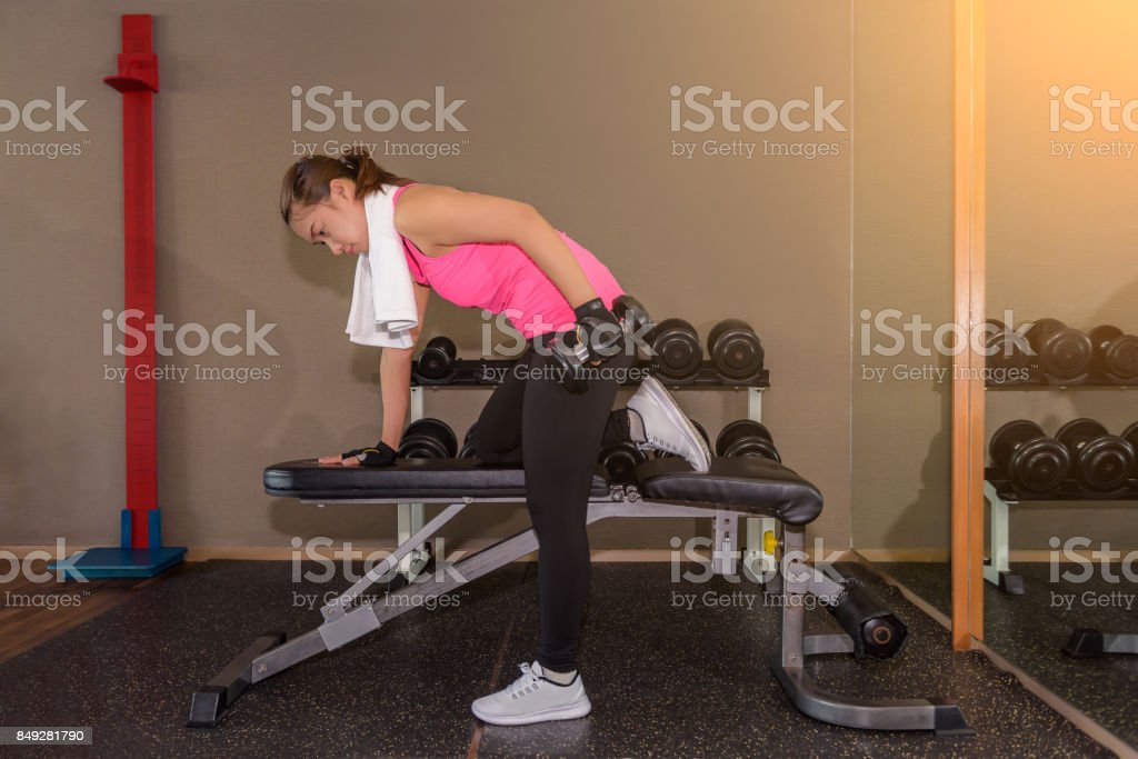 Fitness gym woman strength training lifting dumbbell weights in Bent-over One-Arm Dumbbell Row stock photo