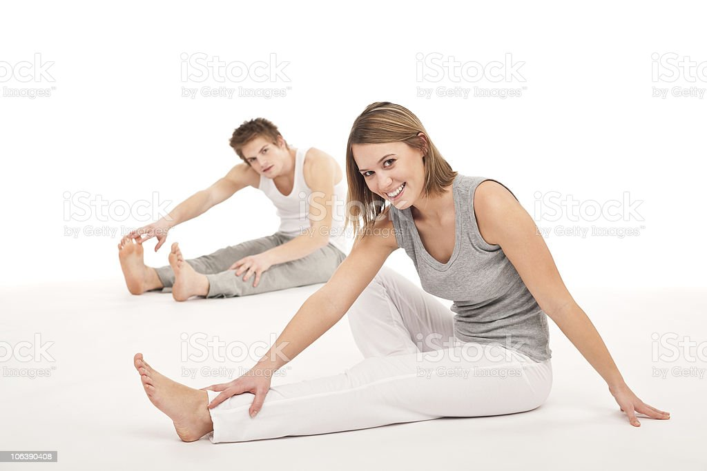 Fitness - Healthy couple stretching after training on white royalty-free stock photo