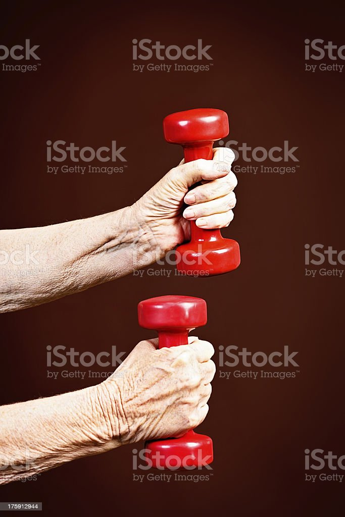 Fitness in old age is vital; elderly arms pump iron royalty-free stock photo