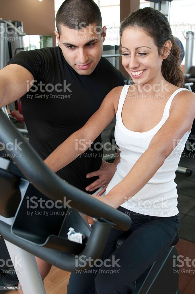 fitness instructor and a young lady in gym royalty-free stock photo