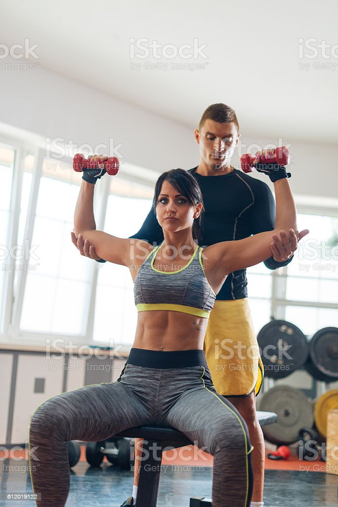 Fitness instructor and trainee exercising with small weights in gym stock photo