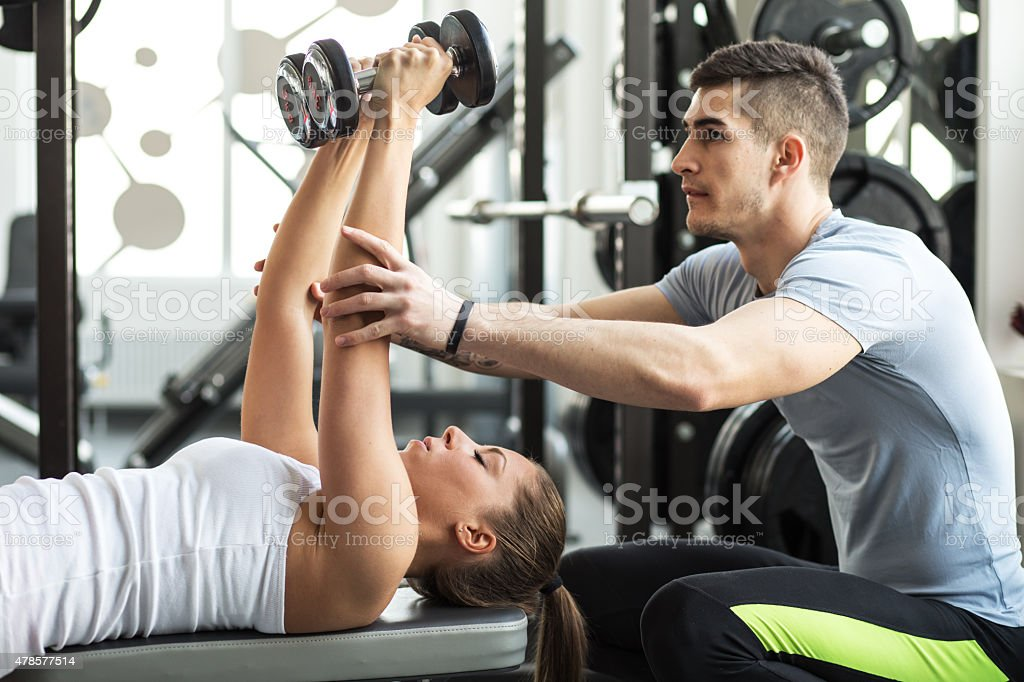 Fitness instructor exercising with his client at the gym stock photo