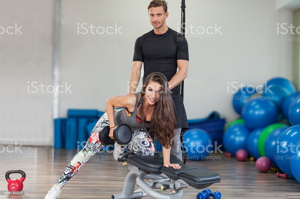 Fitness instructor exercising with his client stock photo
