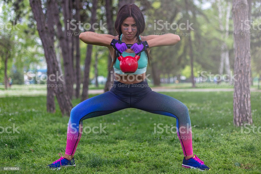 fitness instructor exercising with kettlebell outdoors stock photo