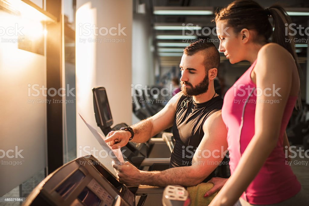 Fitness instructor making a plan with a woman on treadmill. stock photo