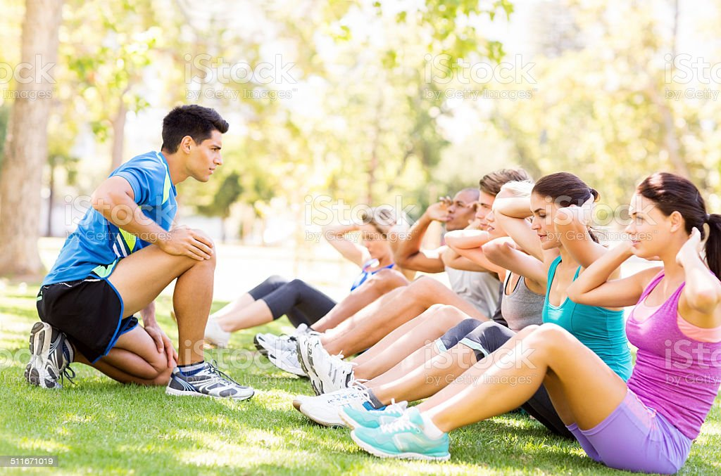 Fitness Instructor Motivating People In Doing Sit-Ups At Park stock photo
