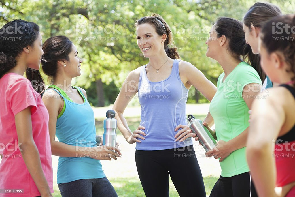 Fitness instructor with her class outside at a park royalty-free stock photo