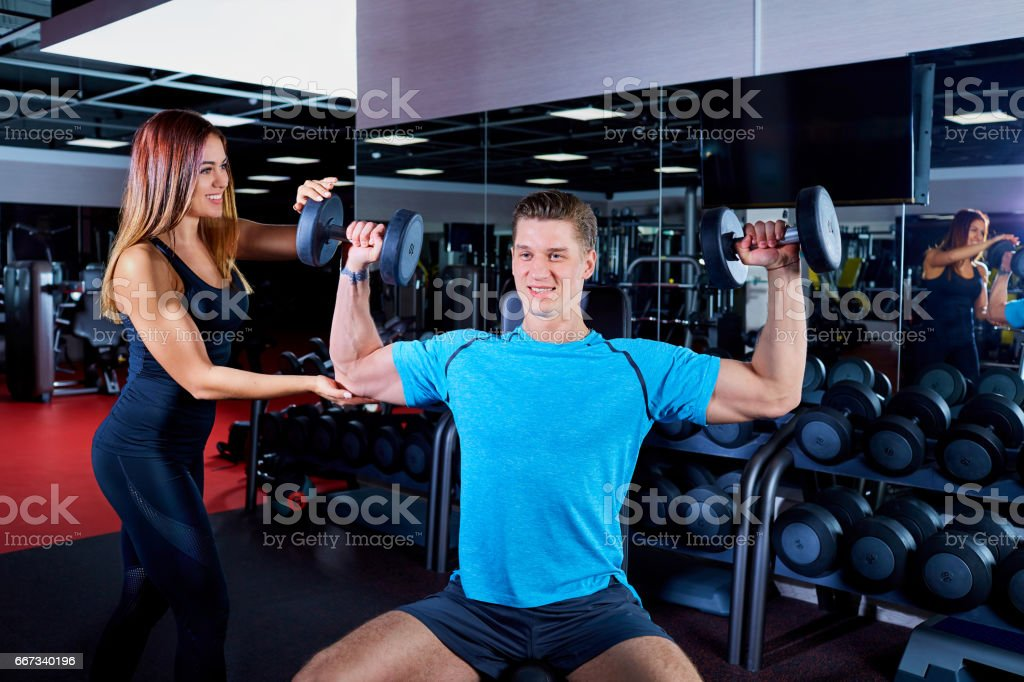 Fitness  instructor woman exercising with his client at the gym. stock photo