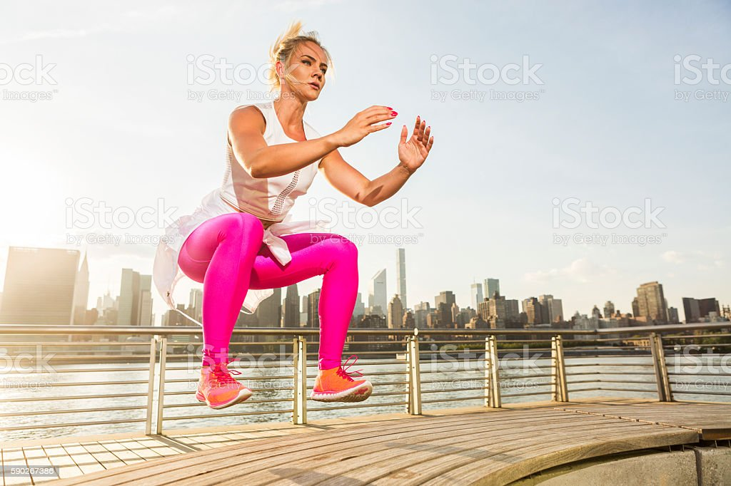 Fitness instructor working out in the park by the river stock photo