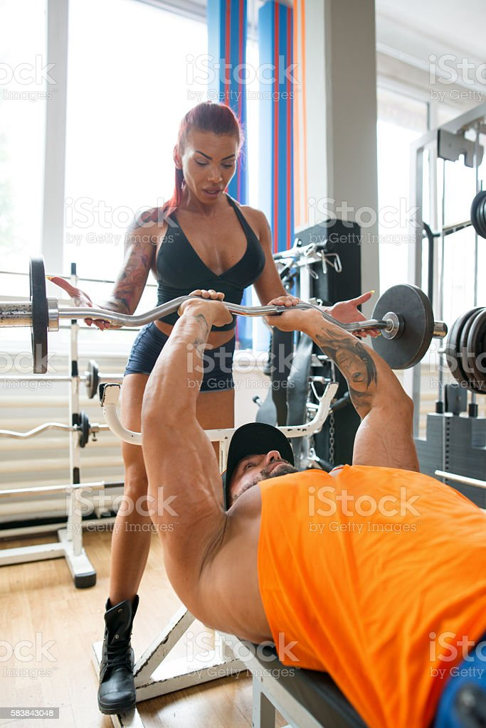 Fitness man and woman training together at the gym stock photo