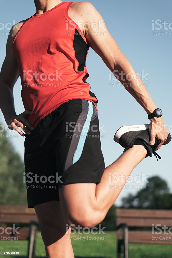 Fitness man close up stretching legs before outdoor workout. stock photo