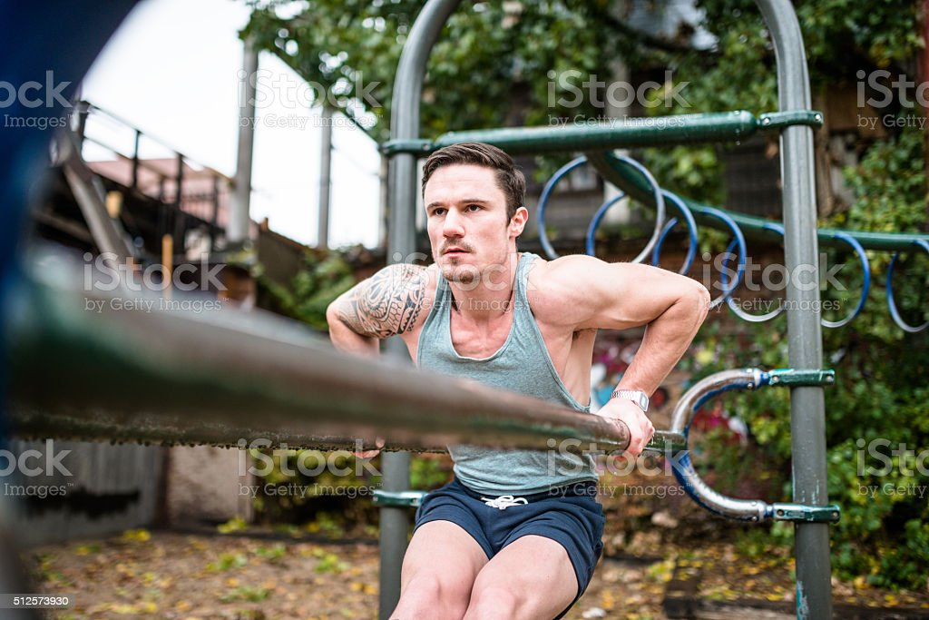 Fitness man doing exercise on the bar at park stock photo