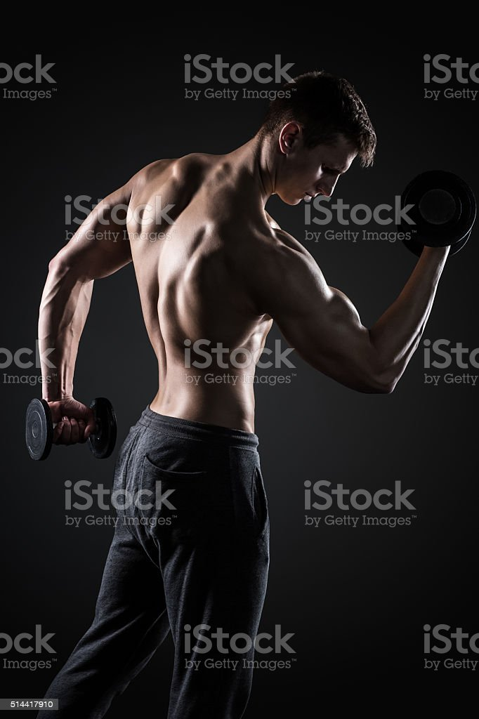Fitness man doing exercises with dumbbells at biceps, rear view stock photo