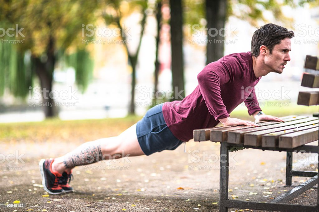 Fitness man doing push-ups at the outdoors park stock photo