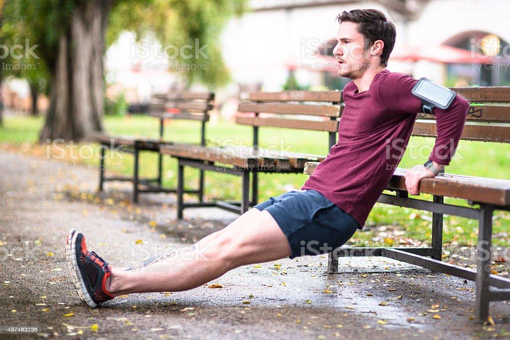 Fitness man doing push-ups at the outdoors park stock photo