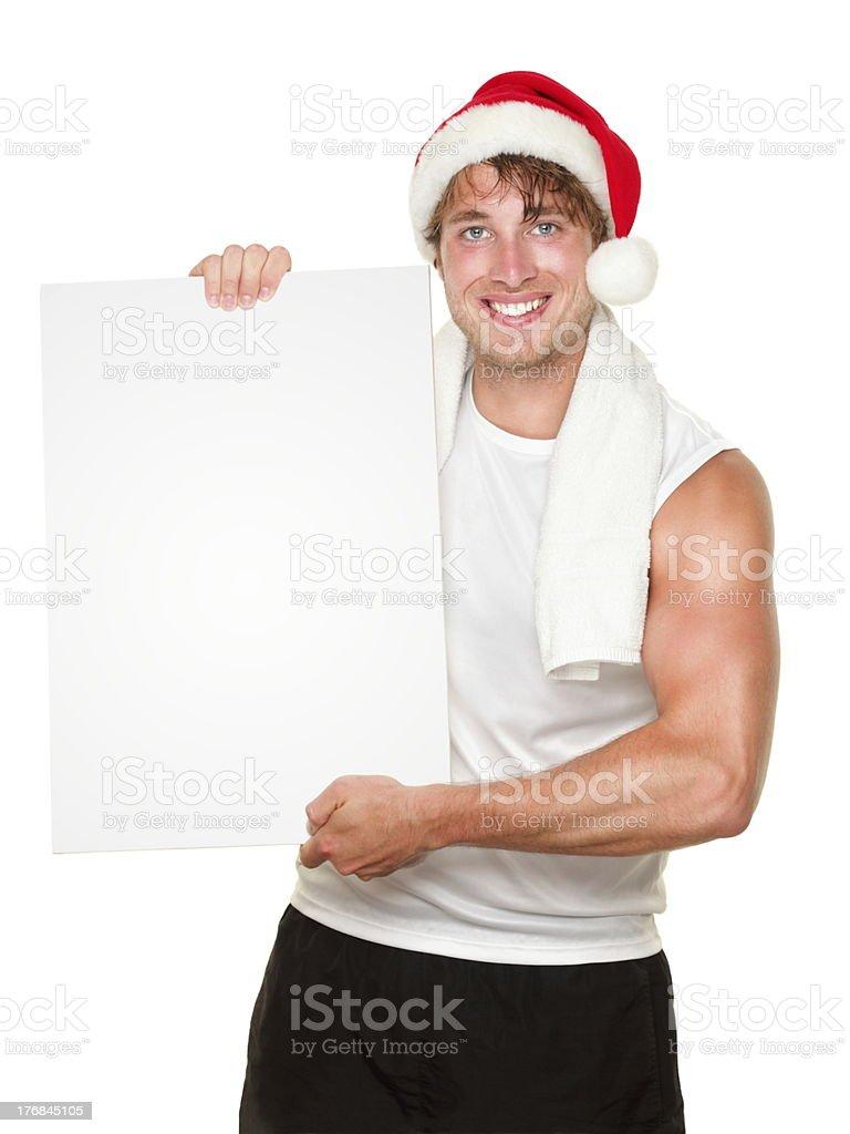 Fitness man holding sign wearing christmas santa hat royalty-free stock photo