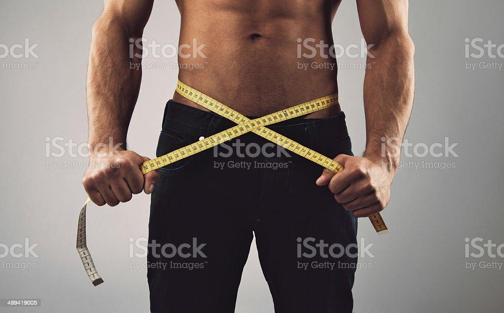 Fitness man measuring his waist stock photo