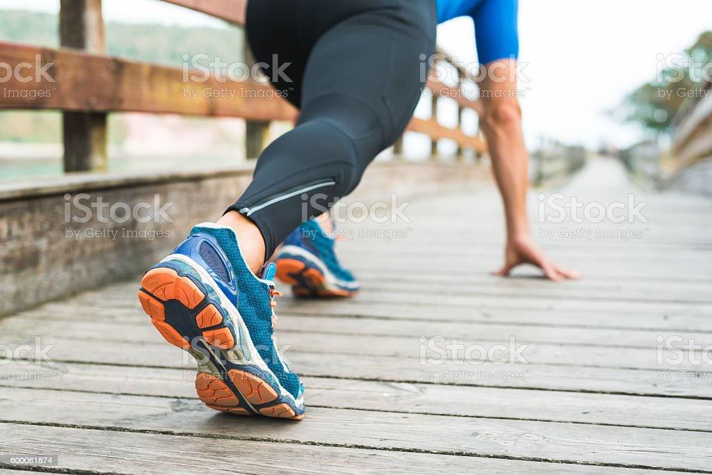 Fitness man ready for running on wooden walkway on park stock photo