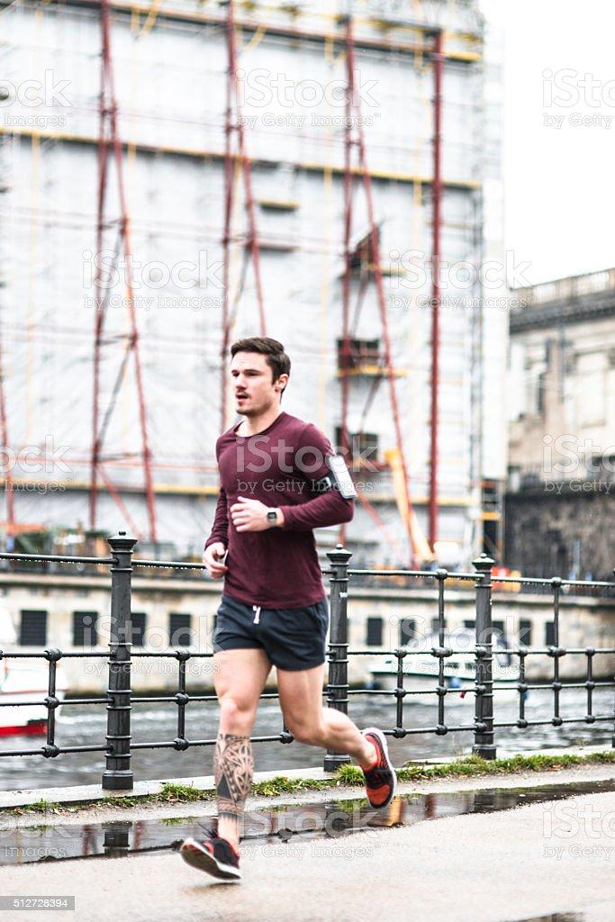 Fitness man running in Berlin under the rain stock photo