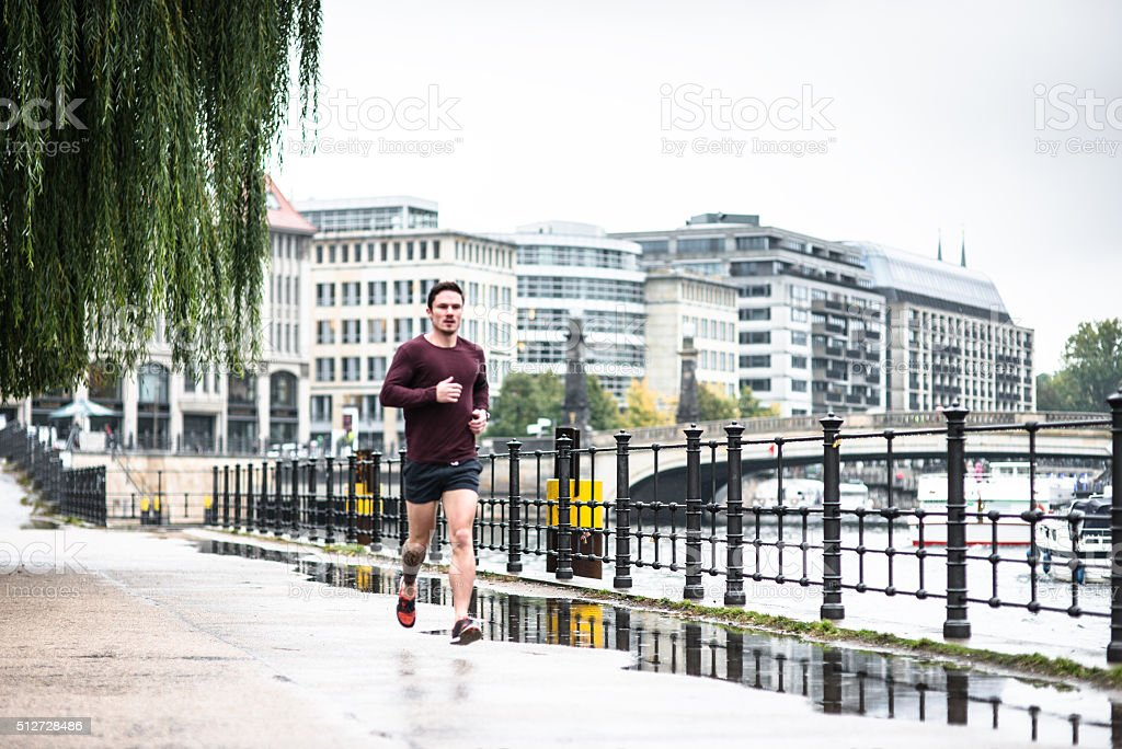 Fitness man running in Berlin under the rain stock photo