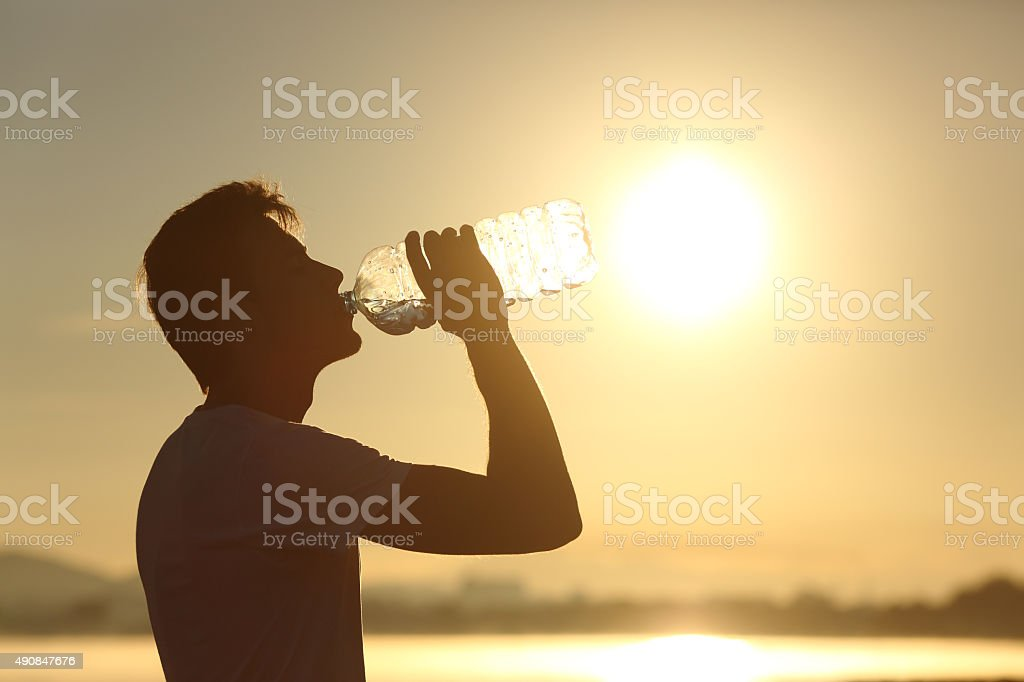 Fitness man silhouette drinking water from a bottle stock photo
