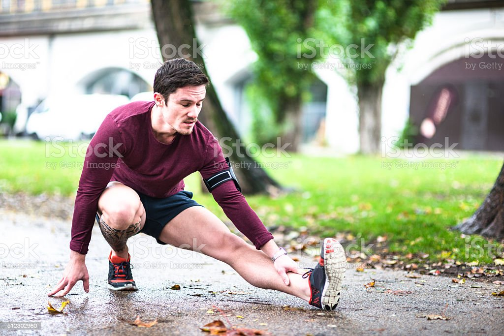 Fitness man stretching the calf in berlin after run stock photo