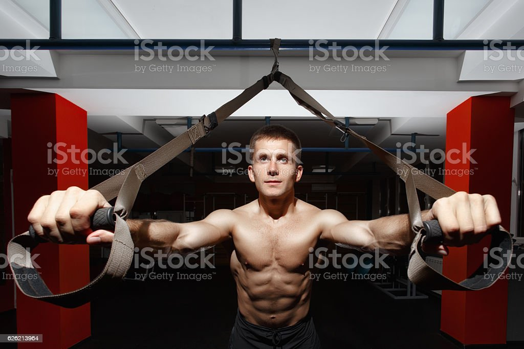 Fitness man workout on the rings in the gym stock photo